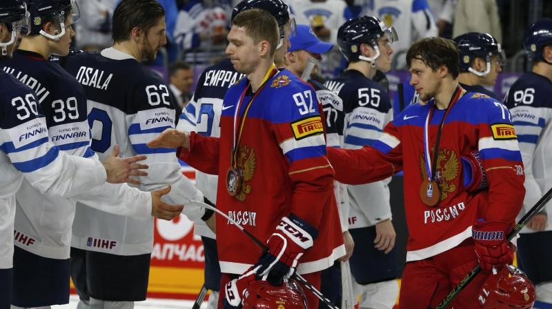 Jevgeņijs Kuzņecovs un Artemijs Panarins ar medaļām kaklā atsveicinās no Somijas izlases hokejistiem Foto: Reuters/Scanpix