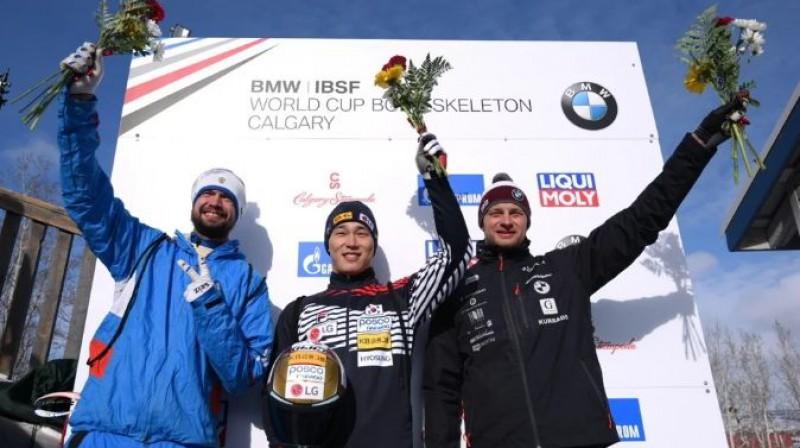 Tomass Dukurs blakus olimpiskajiem čempioniem uz goda pjedestāla Kalgari. Foto: IBSF