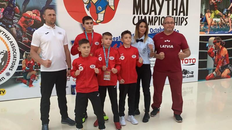 Latvijas jaunie sportisti, viņu treneris Timurs Galejevs, sacens;ibu tiesnesis Tamāra Prokofjeva un delegācijas vadītājs Vasilijs Fleišers.