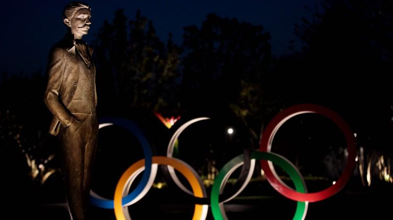Pjēra de Kubertēna statuja blakus olimpiskajiem riņķiem. Foto: AFP/Scanpix